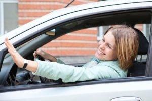 women waving from car